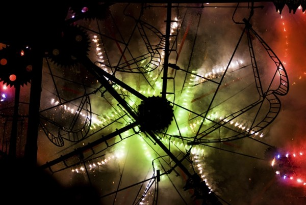 The intricate gears and framework of catherine wheels silhouetted by the flare and spark of another catherine wheel behind it.