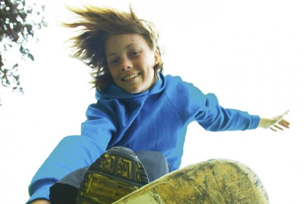 AEGY1X YOUNG TEENAGE GIRL ON A SKATEBOARD DOING AN AERIAL LEAP